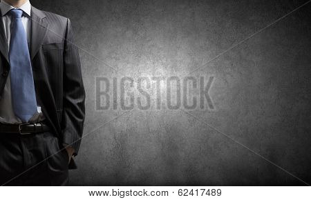 Chest view of businessman against cement wall