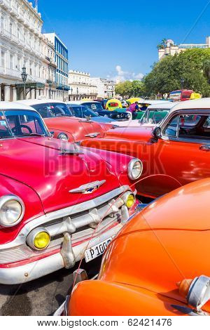 HAVANA, CUBA - FEBRUARY 25, 2014: Colorful group of classic american cars in Old Havana. Thousands of these cars are still in use in Cuba and have become a worlwide known icon of the country