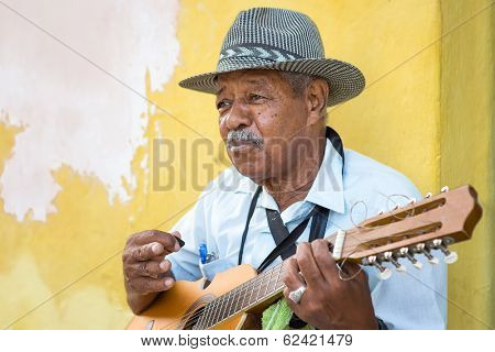 HAVANA, CUBA -?? FEBRUARY 25, 2014: Street musician playing traditional cuban music on an acoustic guitar for the entertainment of tourists in a typical colorful Old Havana street