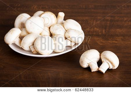 Fresh raw mashroom lying on a plate. Over wooden background.