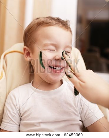 Little boy laughing as mother paints his face