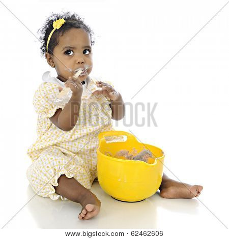 An adorable baby girl looking up questioningly while eating pudding from a mixing bowl before her.  On a white background.