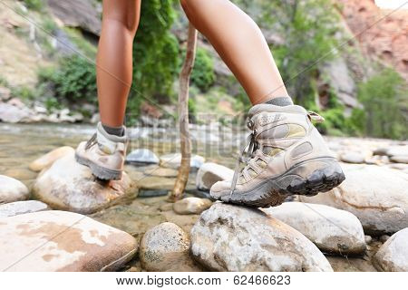 Hiking shoes on hiker outdoors walking crossing river creek. Woman on hike trekking in nature. Close up of female hiking boots in action.