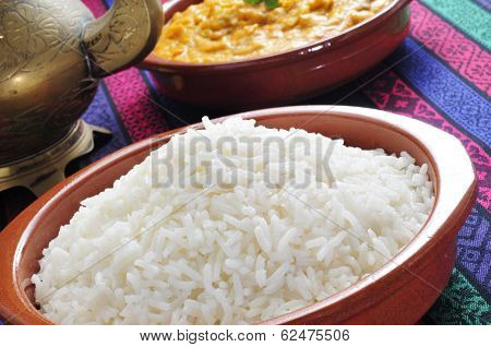 closeup of an earthenware bowl basmati rice and a bowl with korma curry in the background on a set table