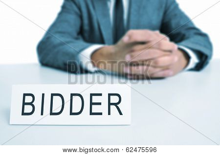 a man wearing a suit sitting in a desk with a desktop nameplate in front of him with the word bidder