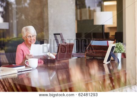 Senior Woman Putting Letter Into Keepsake Box