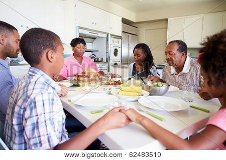 Multi-Generation Family Saying Prayer Before Eating Meal