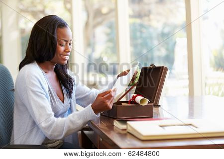 Woman Looking At Letter In Keepsake Box On Desk