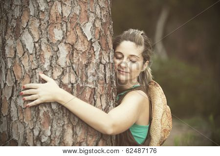 Young woman enjoying nature, embracing a tree trunk