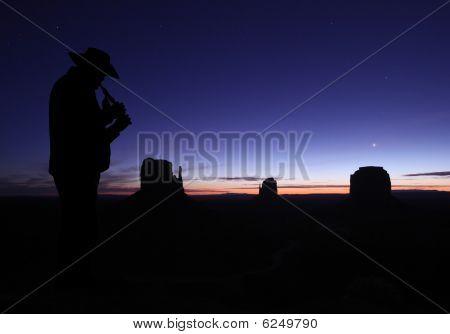 Man Playing Flute In Desert At Dusk