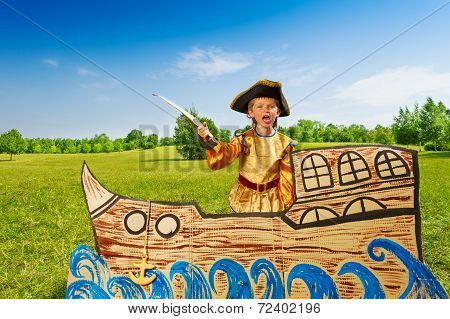 Angry boy in pirate costume shouts and holds sword