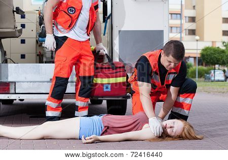 Two paramedics applying first aid unconscious girl poster