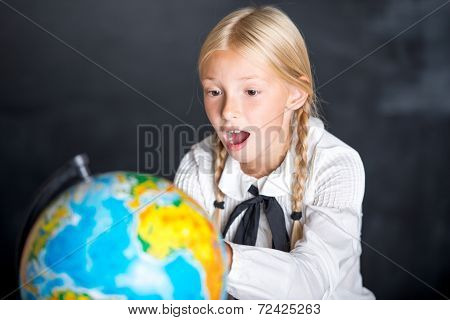 Surprised school girl with globe