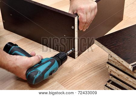 Furniture Assembly Using A Cordless Screwdriver, Close Up.