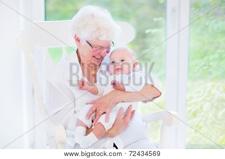Loving Grandmother Singing A Song To Her Newborn Baby Grandson Sitting In A White Rocking Chair