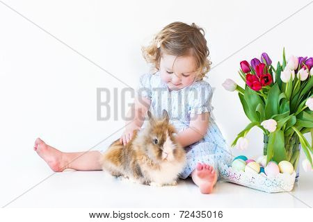 Cute Toddler Girl Playing With A Bunny On Easter Next To A Basket With eggs And Tulip Flowers