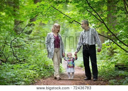 Young Active Grandparents Hiking With Their Baby Grand Daughter In A Park