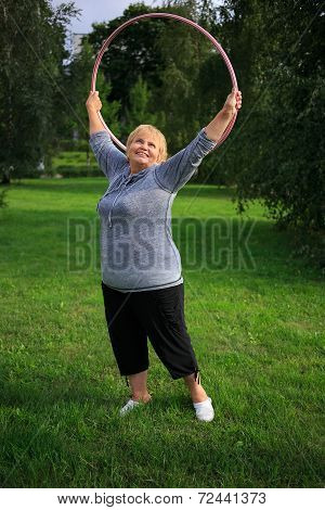 Senior lady doing gymnastic with hula-hoop in the park