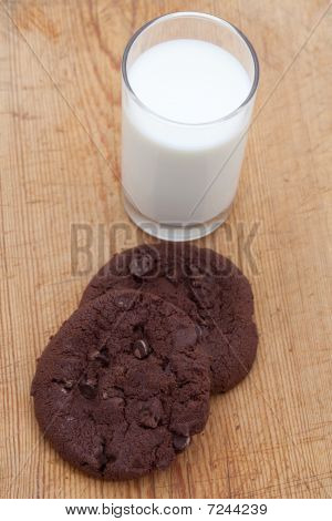 Two Large Chocolate Chip Cookies With A Glass Of Milk