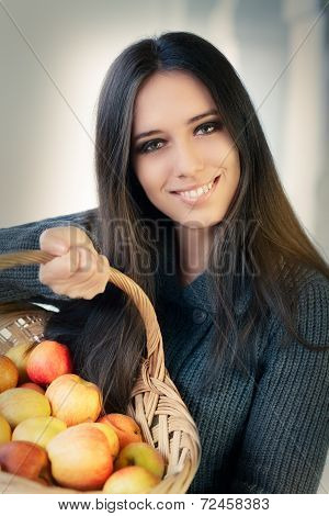 Young woman with a basket of ripe apples