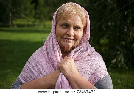 Portrait of  pretty senior woman in the scarf  on nature background