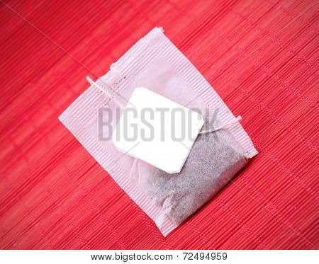 Tea Bag On A Red Striped Background.