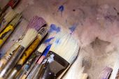 collection of various artists brushes in all sizes on a canvas background poster