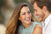 Funny couple laughing with a white perfect smile and looking each other outdoors with unfocused background poster