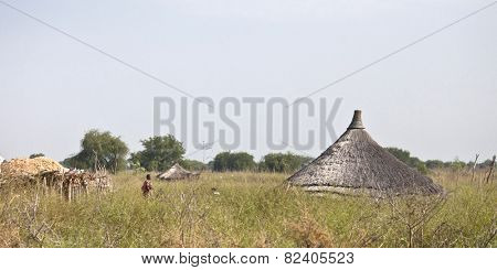 JONGLEI, SOUTH SUDAN-DECEMBER 4, 2010: Unidentified woman walks through a rural village in Jonglei country, South Sudan