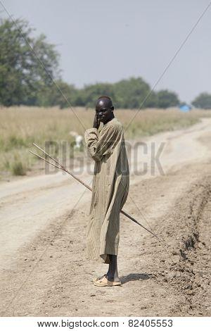 JONGLEI, SOUTH SUDAN-DECEMBER 4, 2010: Unidentified shepherd walks down the road in Jonglei county, South Sudan