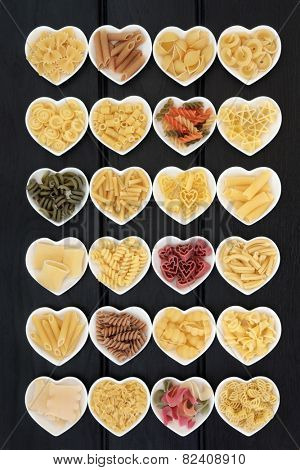 Large pasta food selection in heart shaped porcelain dishes over dark wood background. poster