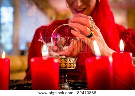 Fortuneteller or esoteric Oracle, sees in the future by looking into their crystal ball, incense burning and candles giving light poster