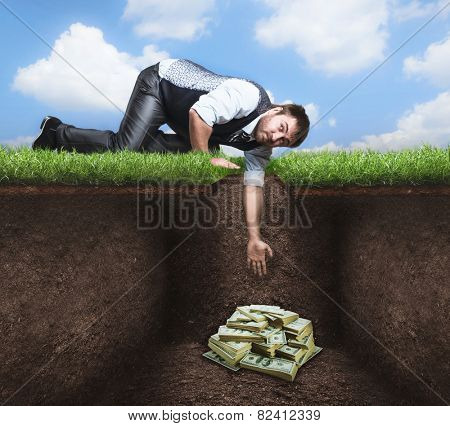 Businessman trying to get treasure in the soil