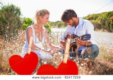 Handsome man serenading his girlfriend with guitar against hearts hanging on a line