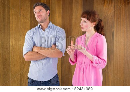 Woman arguing with uncaring man against wooden surface with planks