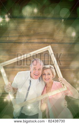 Older couple smiling at camera through picture frame against light design shimmering on green