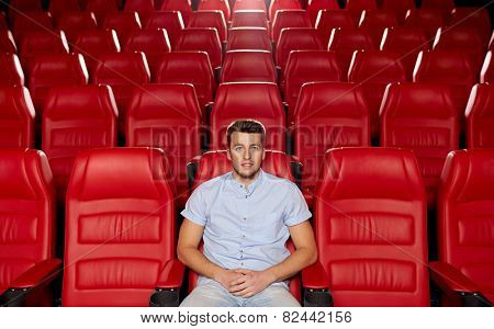 cinema, entertainment and people concept - happy young man watching movie alone in empty theater auditorium poster