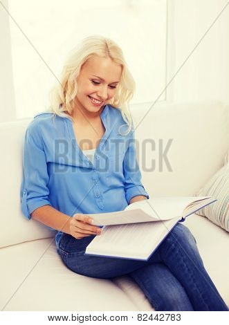 leasure and home concept - smiling middle-aged woman reading book and sitting on couch at home