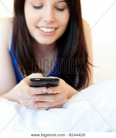 strahlende junge Frau Texting beim liegen auf einem Bett