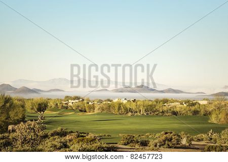 Scottsdale, Phoenix area golf course with dramatic unusual low lying fog in below mountain peaks in distance