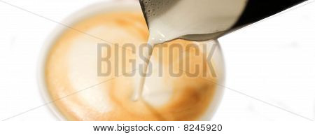 Barista Pouring Milk into a Coffee