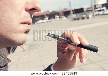 a young man vaping with an electronic cigarette