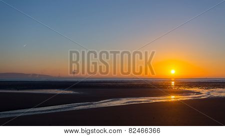 Sunrise over Swansea beach, South Wales, on a clear winter morning, with the industrial emissions from Port Talbot visible across the bay and a plane's contrail in the sky.