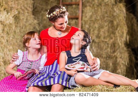 Bavarian family sitting on hayloft with gingerbread