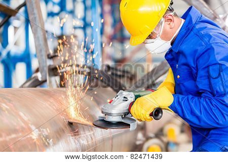 Industrial worker in manufacturing plant grinding to finish a pipeline