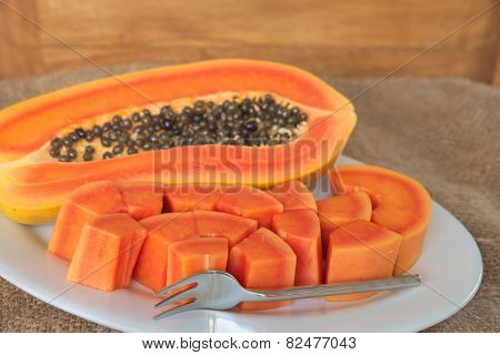 Papaya slice with silver dessert fork on white dish over grunge sack with wooden background