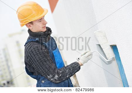 builder worker painting facade of high-rise building with roller poster
