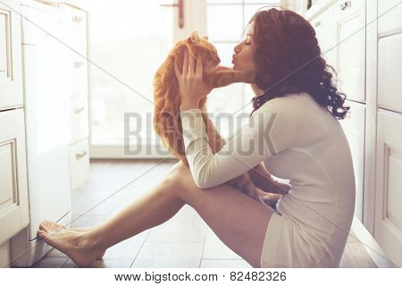 Young lady kissing cat on the floor at the kitchen at home