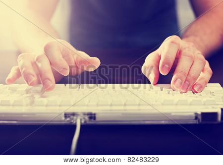hands typing on laptop keyboard toned with a retro vintage instagram filter