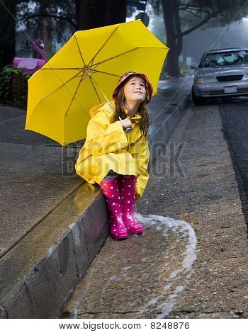 Young girl playing in rain with umbrella 4